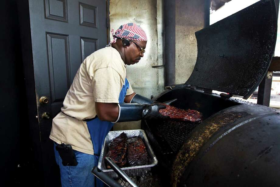 Trent Brooks, owner of Brooks Place BBQ pulls meat from his smoker before he opens his barbecue joint for business, Friday, June 21, 2013, in Cypress. ( Nick de la Torre / Houston Chronicle ) Photo: Nick De La Torre, Staff / © 2013  Houston Chronicle