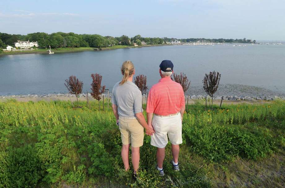 Greenwich residents, Paul and Maureen Colligan, husband and wife, hold hands at they look toward Cos Cob Harbor during the announcement of a proposed memorial to Sept. 11 victims at the Cos Cob Power Plant site, Tuesday evening, June 25, 2013. Maureen Colligan lost her brother, Kevin Cleary, who was a victim of the 9/11 terrorist attacks. Photo: Bob Luckey / Greenwich Time
