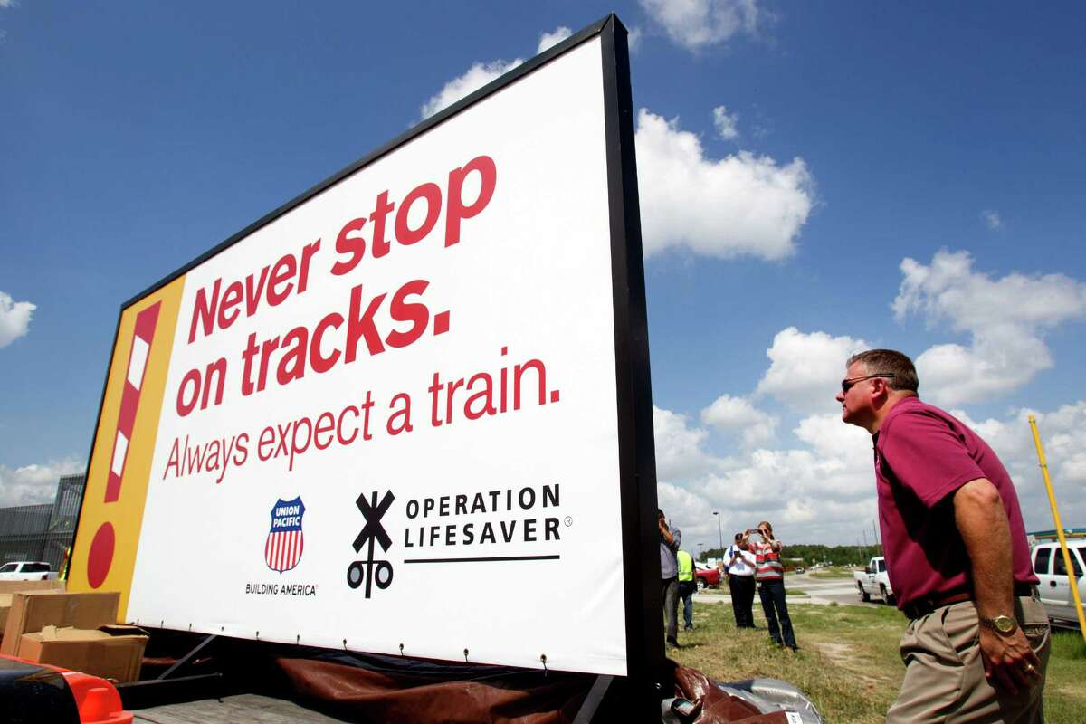 Union Pacific Railroad official Jason Jenkins, right, is hoping that two recently unveiled large signs will reduce vehicle-train accidents at a crossing in the 800 block of Richey Road along the Hardy Toll Road.