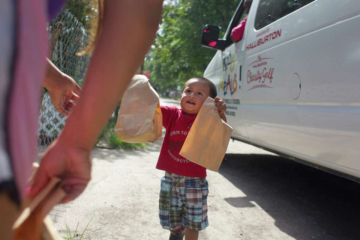 Matthew Zuniga, 18 months old, brings his mother prepared lunches for himself and his four-year-old brother that was delivered to him from the organization Kids' Meals Tuesday, June 25, 2013, in north Houston.