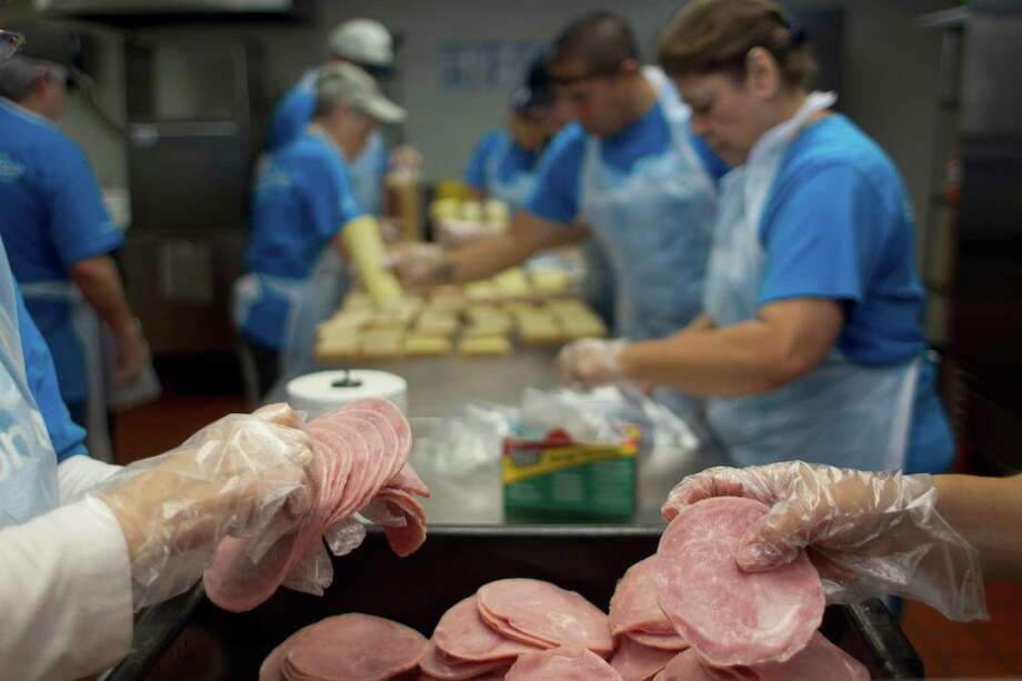 Volunteers from Marathon Oil make prepared lunches that will be delivered to preschool aged children living in poverty from the organization Kids' Meals Tuesday, June 25, 2013, in north Houston. Photo: Johnny Hanson, Houston Chronicle / © 2013  Houston Chronicle