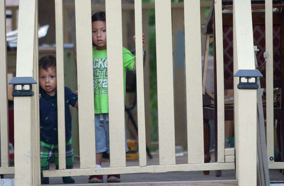 After hearing a vehicle beep its horn down the street, Jonathan Rivera, 3, and his brother, Johan, 1, wait for the Kids' Meals van that will bring them prepared lunches Tuesday, June 25, 2013, in north Houston. Photo: Johnny Hanson, Houston Chronicle / © 2013  Houston Chronicle