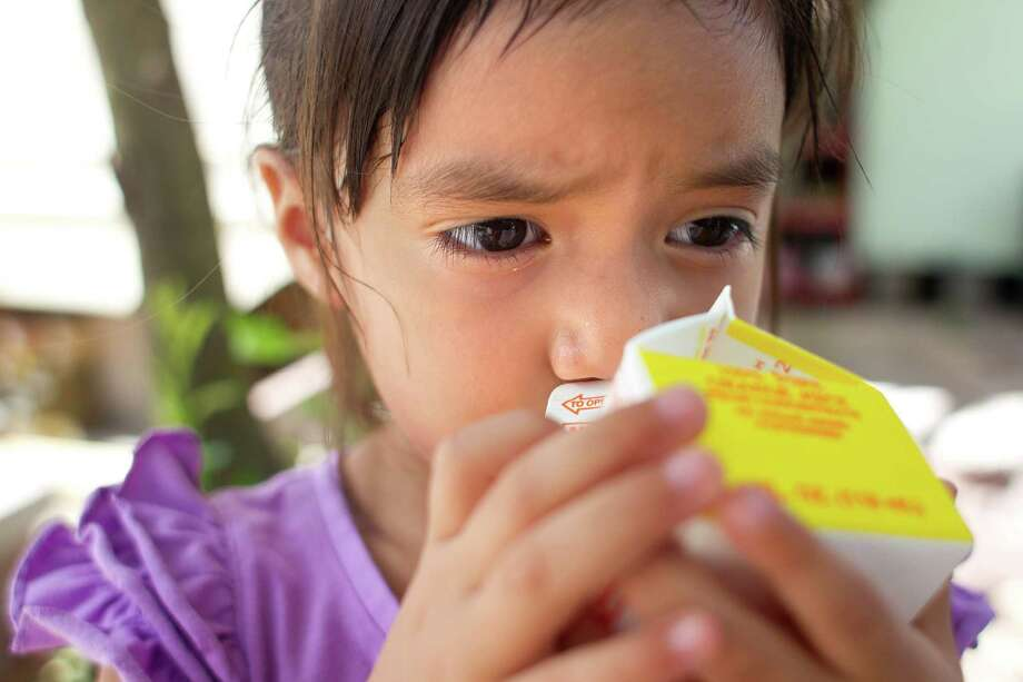 Adrina Martinez, 3, drinks a milk that was delivered to her with a prepared lunch from the organization Kids' Meals Tuesday, June 25, 2013, in north Houston. Photo: Johnny Hanson, Houston Chronicle / © 2013  Houston Chronicle