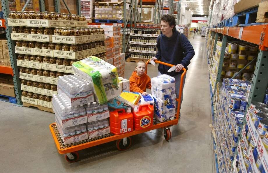 Shopping in bulk with monster carts take a long time, especially when Costco purposely doesn't label its aisles. That - along with no shopping bags, advertising and credit-card machines, helps keeps costs low. Photo: Tim Boyle, Getty Images / Getty Images North America