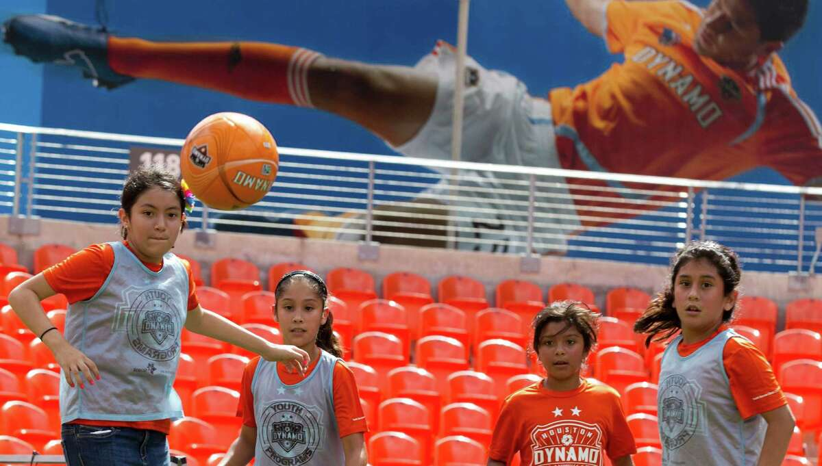 Yasmine de la Rosa, left, Abigail Carrizales, Savannah Becerra and Sophia Paredes go after a ball as they play soccer at BBVA Compass stadium Tuesday, June 25, 2013, in Houston. Children from Ripley House Community Center ran drills with trainers and played games against each other on the stadium floor.