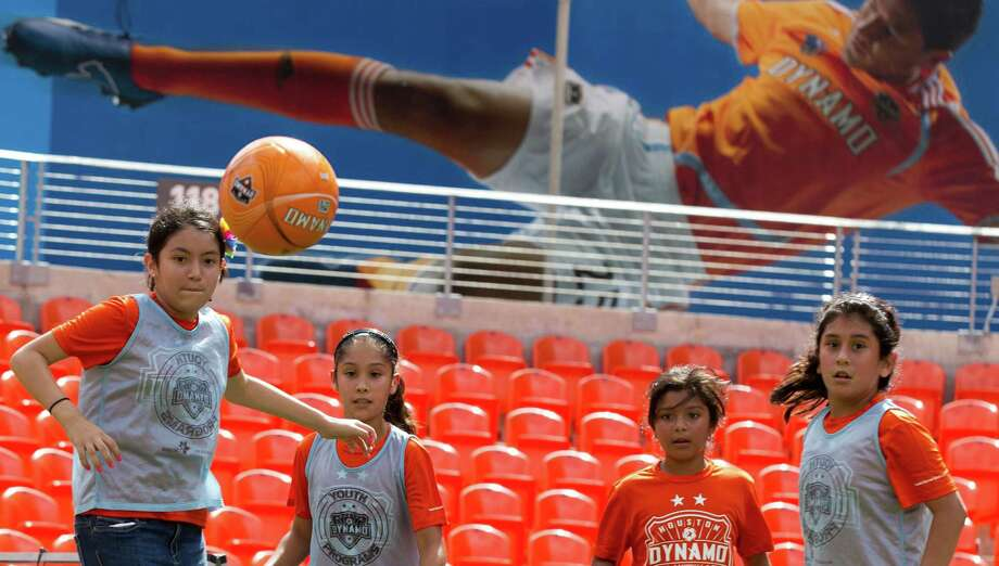 Yasmine de la Rosa, left, Abigail Carrizales, Savannah Becerra and Sophia Paredes go after a ball as they play soccer at BBVA Compass stadium Tuesday, June 25, 2013, in Houston. Children from Ripley House Community Center ran drills with trainers and played games against each other on the stadium floor. Photo: Brett Coomer, Houston Chronicle / © 2013 Houston Chronicle