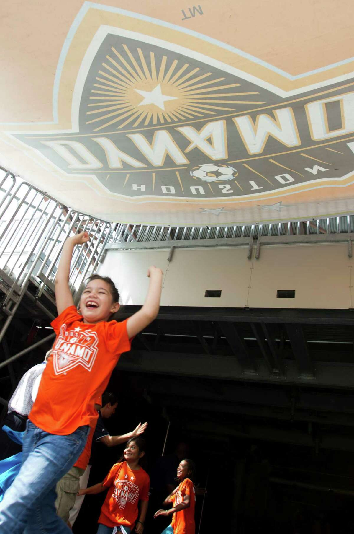 Isabella Fernandez cheers as she runs through the tunnel to play soccer at BBVA Compass Stadium with her classmates from Ripley House Community Center Tuesday, June 25, 2013, in Houston. The children ran drills and played games on the stadium floor.