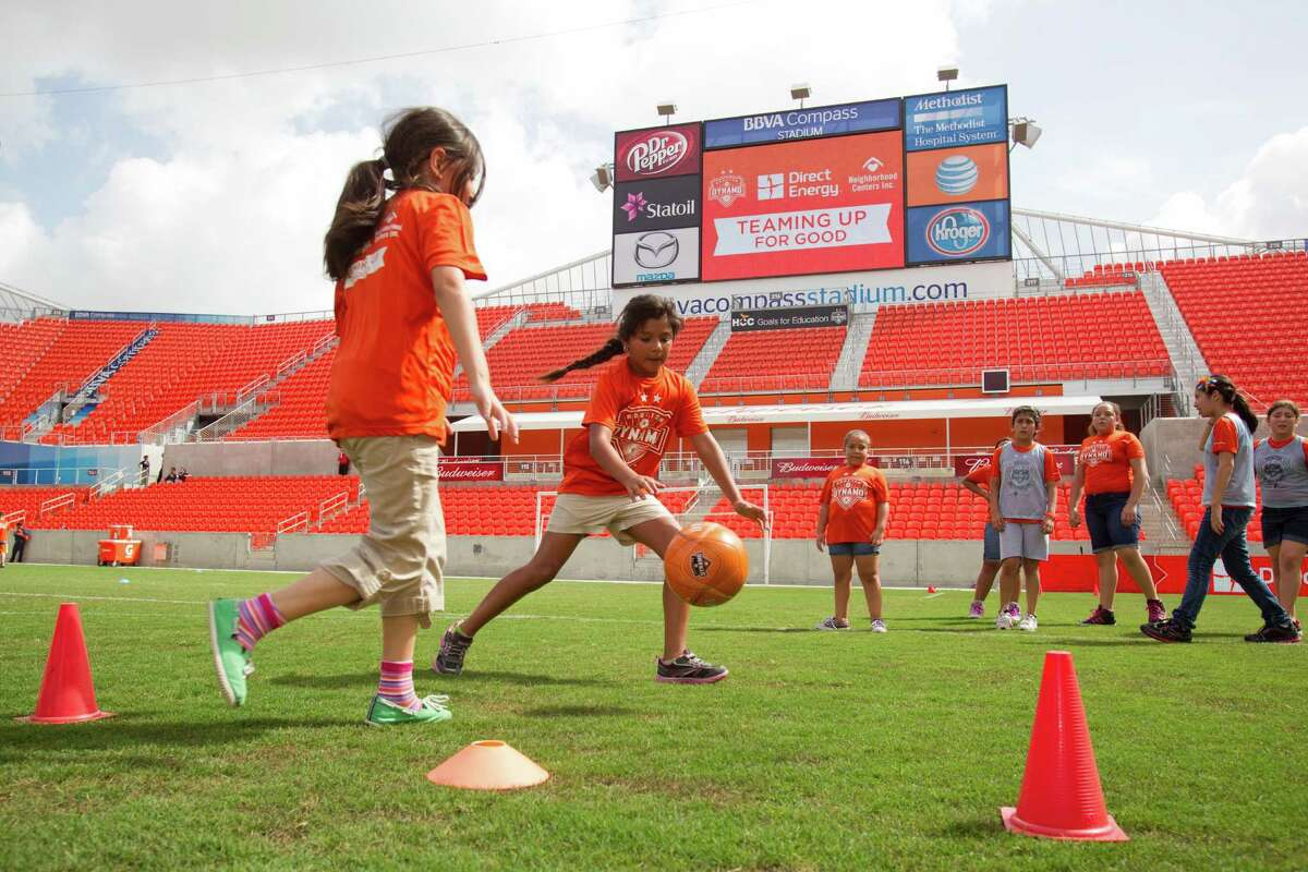 Bella Vasquez, left, runs over to defend a shot on goal by Savannah Becerra, center, while playing soccer at BBVA Compass stadium Tuesday, June 25, 2013, in Houston. Children from Ripley House Community Center ran drills with trainers and played games against each other on the stadium floor.