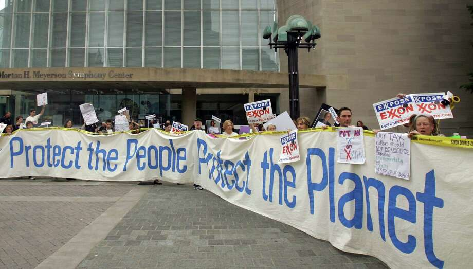 Protesters carry a banner outside the Morton H. Meyerson Symphony Center in Dallas, where the Exxon Mobil shareholders meeting was held last month. Photo: LM Otero, STF / AP