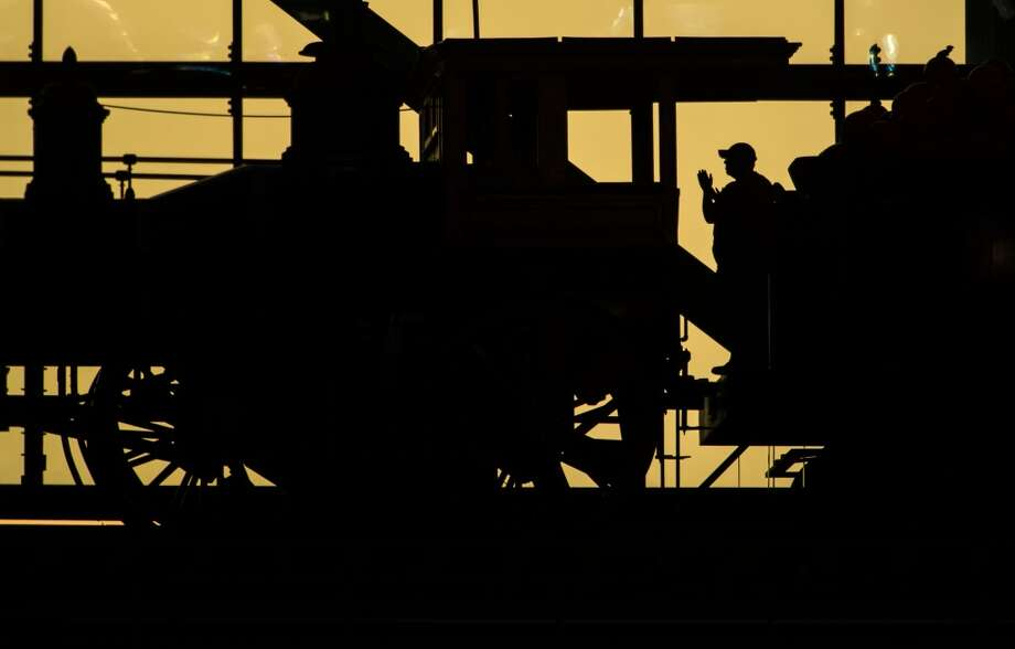 Minute Maid Park train conductor Bobby Vasquez is silhouetted against the sunset outside the stadium during the third inning.