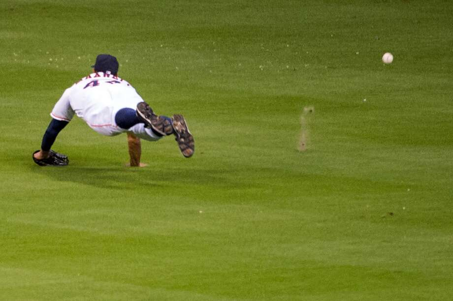 Astros right fielder Justin Maxwell dives for a bases-loaded triple off the bat of Cardinals second baseman Matt Carpenter during the fourth inning.