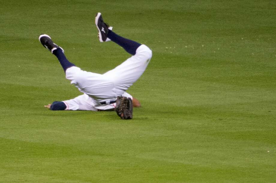 Astros right fielder Justin Maxwell crashes into the turf as he dives for a bases-loaded triple off the bat of Cardinals second baseman Matt Carpenter during the fourth inning.