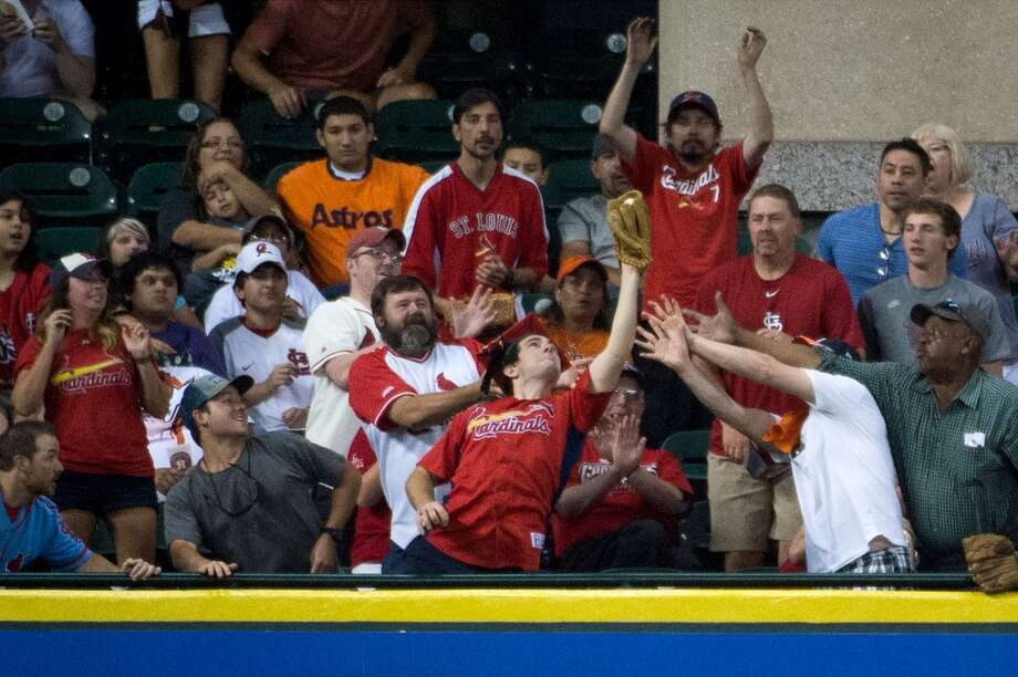 A Cardinals fan in the Crawford Boxes makes the grab on a home run by Cardinals right fielder Carlos Beltran during the sixth inning.