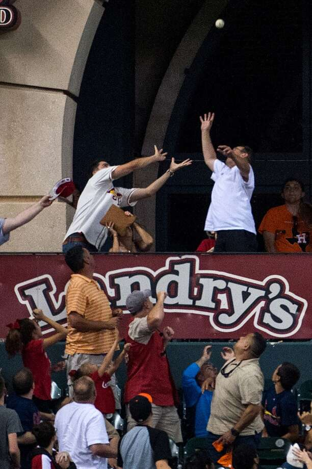 Fans in the Crawford Boxes reach for a home run off the bat of Cardinals third baseman David Freese during the seventh inning.