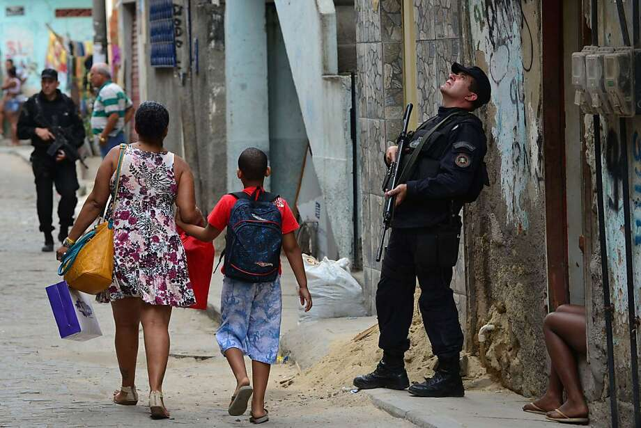 Officers with a special operations force known under the acronym BOPE patrol the streets of Nova Holanda shantytown, in the violence-plagued Mare complex on June 25, 2013, a day after gunbattles erupted in the slum complex in Rio de Janeiro. Seven people, including one police officer, were fatally shot during confrontations in a favela near Rio's international airport, authorities said on Tuesday. Brazil is currently facing unprecedented social unrest, marked by almost daily street protests to demand better public services and an end to rampant political corruption as the FIFA Confederations Cup Brazil 2013 football tournament is being held in the country. AFP PHOTO / YURI CORTEZYURI CORTEZ/AFP/Getty Images Photo: Yuri Cortez, AFP/Getty Images