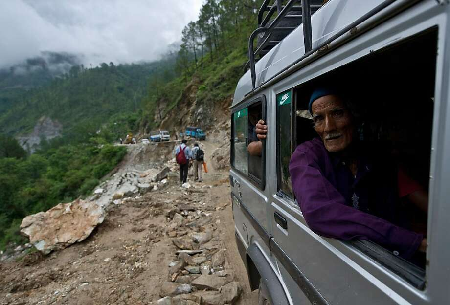 An elderly Indian man looks out as he drives past a damaged section of road between Rudraprayag and Gauchar, at Gauchar on June 25, 2013, after flash flooding hit the northern Indian state of Uttarakhand. Some 1000 people have been killed in flash floods and landslides in northern India, as a top official warned that rebuilding of the devastated Himalayan region would take years. AFP PHOTO/MANAN VATSYAYANAMANAN VATSYAYANA/AFP/Getty Images Photo: Manan Vatsyayana, AFP/Getty Images