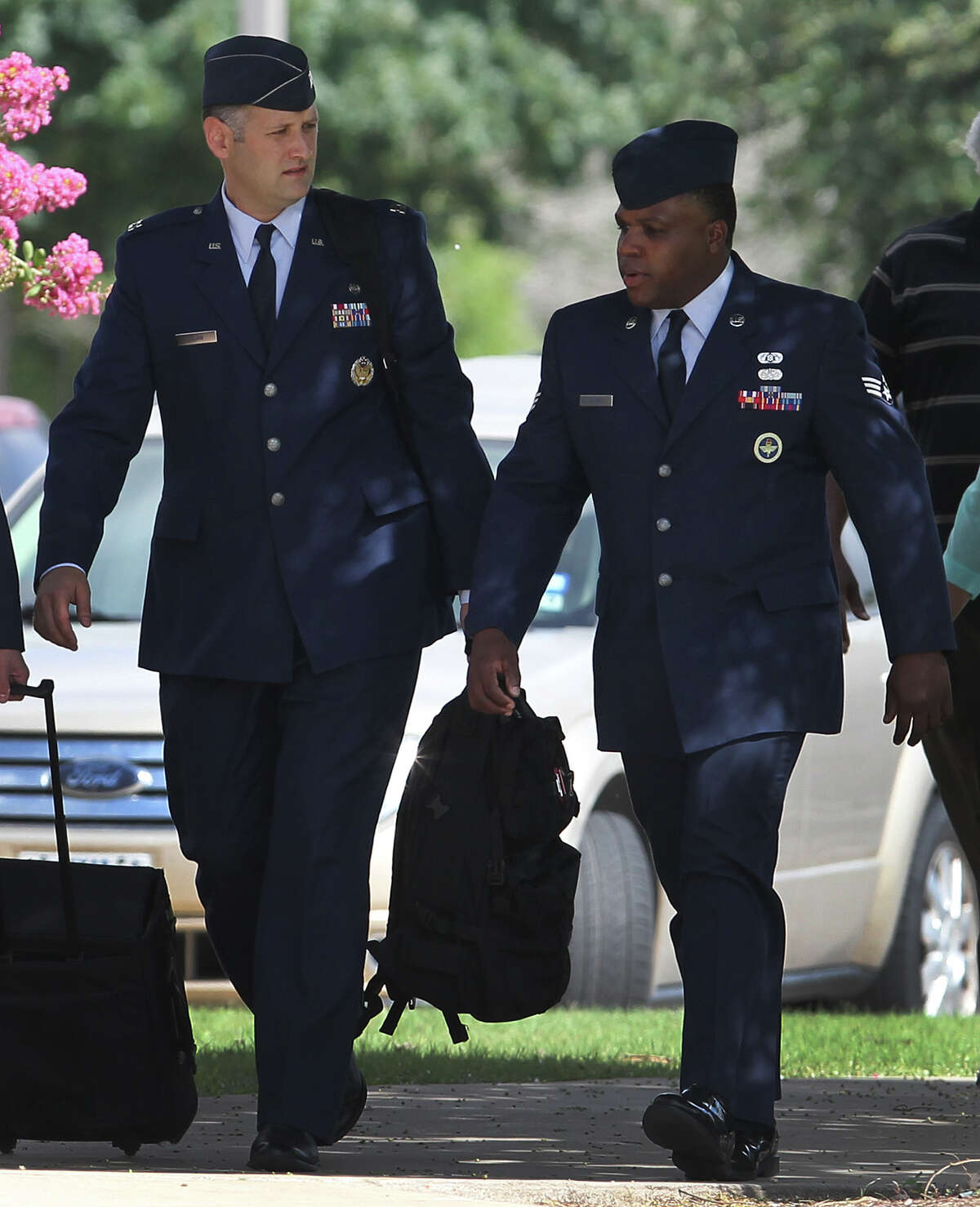 Senior Airman Christopher Oliver (right) walks Monday June 24, 2013 at Joint Base San Antonio-Lackland. Oliver is facing a court-martial on charges of aggravated sexual assault and abusive sexual conduct of one basic training recruit and other charges.