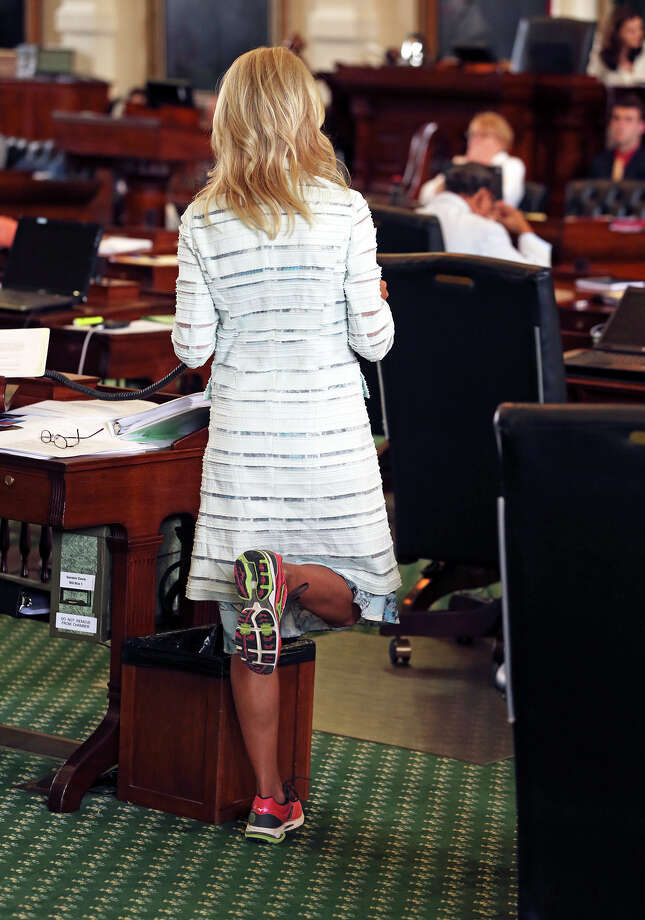 Fort Worth Senator Wendy Davis relieves pressure on her feet as she filibusters in an effort to cause abortion legislation to die without a vote on the floor of the Senate Tuesday, June 25, 2013. Photo: TOM REEL