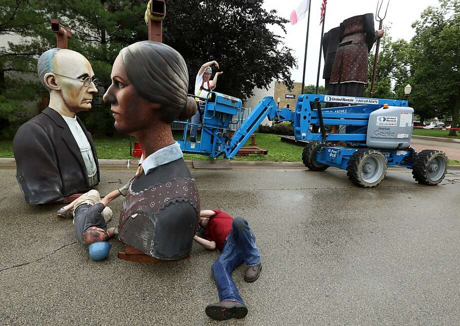 "Crews dismantle Seward Johnson's ""God Bless America"" statue that has been on display outside the Dubuque Museum of Art Tuesday, June 25, 2013. The statue that has been in Dubuque since October of 2010 will move to Simpson College in Indianola, Iowa. (AP Photo/Telegraph Herald, Dave Kettering) Photo: Dave Kettering, Associated Press"