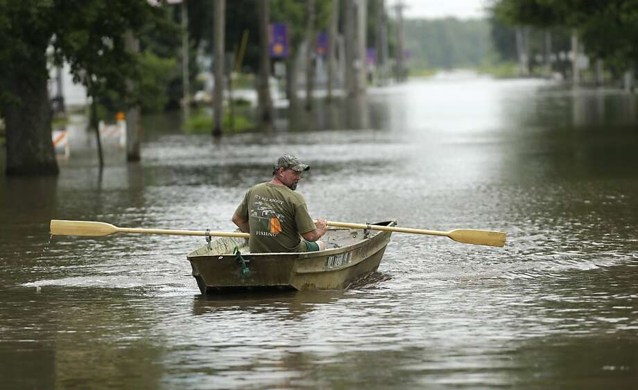 Jim Johnson rows his boat down Main Street, Tuesday, June 25, 2013, in New Hartford, Iowa. Hundreds of residents obeyed an order to evacuate their homes in this northeast Iowa town Tuesday before floodwaters from a rising creek could strand them. (AP Photo/Charlie Neibergall) Photo: Charlie Neibergall, Associated Press