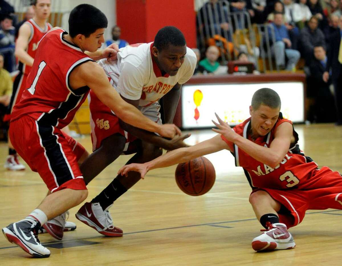 Masuk's #1 Anthony Delorenzo, left, Stratford's #21 Dashawn Moffatt, center, and Masuk's #3 Scott Corchard all go after a loose ball, during basketball action in Stratford, Conn. on Friday Jan. 15, 2010.