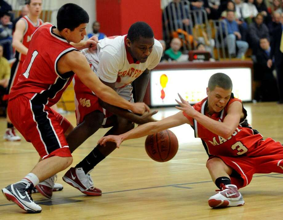 Masuk's #1 Anthony Delorenzo, left, Stratford's #21 Dashawn Moffatt, center, and Masuk's #3 Scott Corchard all go after a loose ball, during basketball action in Stratford, Conn. on Friday Jan. 15, 2010. Photo: Christian Abraham / Connecticut Post