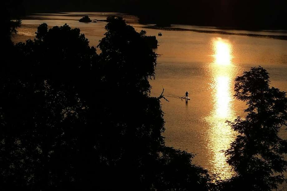 A solo paddle boarder maneuvers down the Potomac River in Washington at sunset Tuesday, June 25, 2013. Temperatures in the Nation's Capital reached the low 90 degrees making a quiet paddle down the river a nice respite from the heat. (AP Photo/J. David Ake) Photo: J. David Ake, Associated Press
