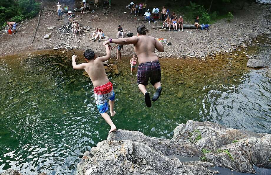 Jose Rivera-Hostos, right, from Winchester and stepson, Vladimir, jump together off of the tallest rock at Blue Hole to cool off on the hot Tuesday, June 25, 2013 in Rawley Springs, Va. (AP Photo/Daily News-Record, Michelle Mitchell) Photo: Michelle Mitchell, Associated Press