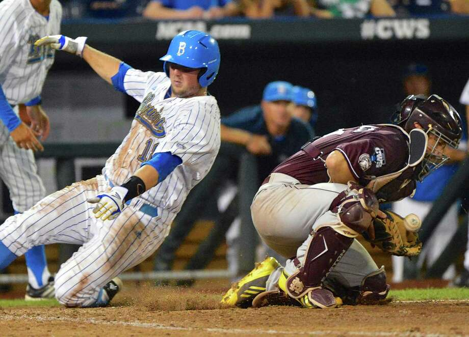 UCLA's Cody Regis, left, slides safely to home plate on a single by Eric Filia ahead of the throw to Mississippi State catcher Nick Ammirati in the sixth inning of Game 2 in their NCAA College World Series baseball finals, Tuesday, June 25, 2013, in Omaha, Neb. (AP Photo/Ted Kirk) ORG XMIT: NENH112 Photo: Ted Kirk / FR34398 AP