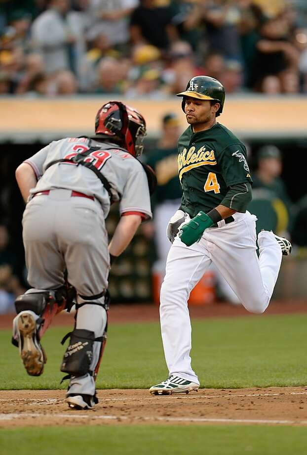 OAKLAND, CA - JUNE 25:  Coco Crisp #4 of the Oakland Athletics scores on an RBI single from Yoenis Cespedes #52 in the third inning against the Cincinnati Reds at O.co Coliseum on June 25, 2013 in Oakland, California.  (Photo by Thearon W. Henderson/Getty Images) Photo: Thearon W. Henderson, Getty Images