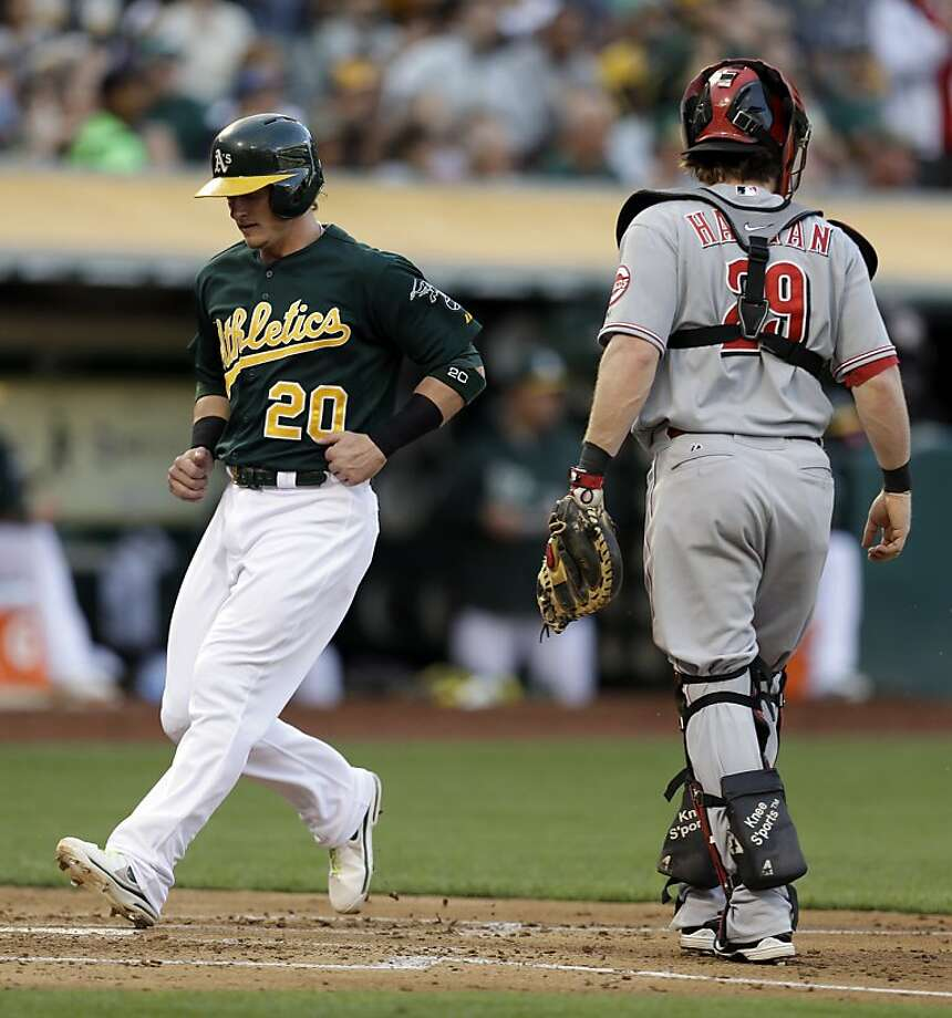 Oakland Athletics' Josh Donaldson, left, scores past Cincinnati Reds catcher Ryan Hanigan in the second inning of a baseball game Tuesday, June 25, 2013, in Oakland, Calif. Donaldson scored on an RBI double by Josh Reddick. (AP Photo/Ben Margot) Photo: Ben Margot, Associated Press