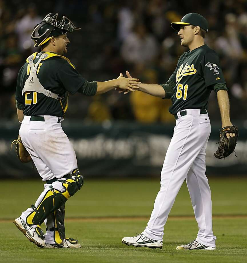 Oakland Athletics' Dan Otero, right, is congratulated by catcher Stephen Vogt at the end of a baseball game against the Cincinnati Reds Tuesday, June 25, 2013, in Oakland, Calif. The A's won, 7-3. (AP Photo/Ben Margot) Photo: Ben Margot, Associated Press