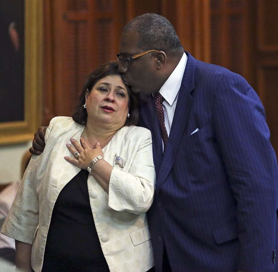 Sen. Leticia Van de Putte is comforted by Sen. Royce West after she arrives in the Senate Tuesday night. Returning from her father's funeral, Van de Putte tried to stop the bill. Photo: TOM REEL, San Antonio Express-News