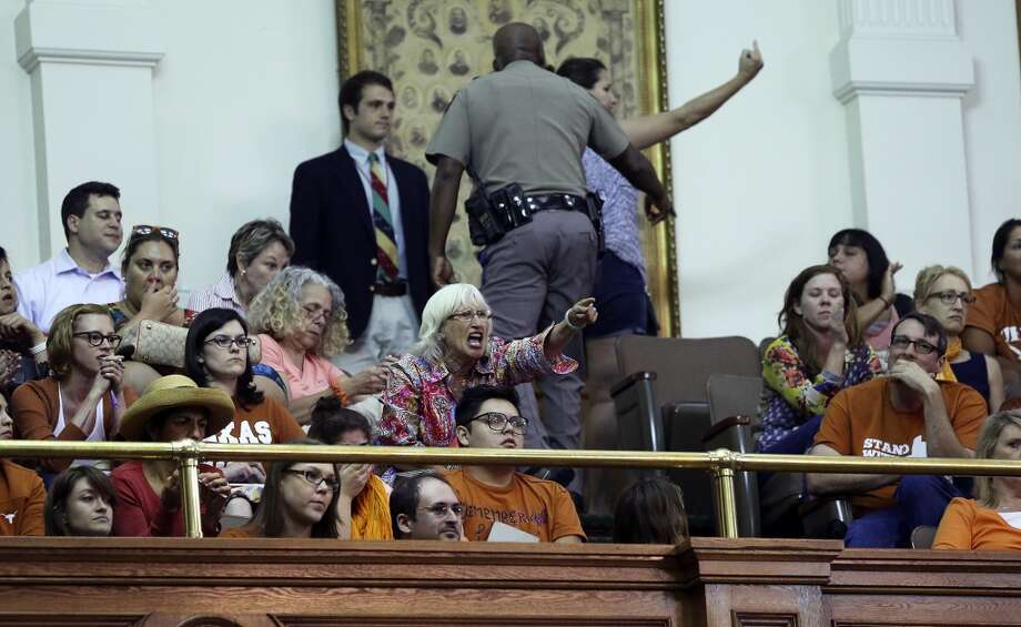 Shouting spectators are removed from the chamber. Photo: TOM REEL, San Antonio Express-News