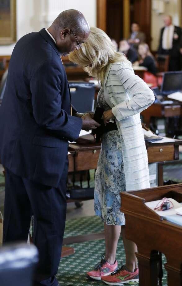 Sen. Rodney Ellis, D-Houston, helps Davis with a back brace. Photo: Eric Gay, Associated Press