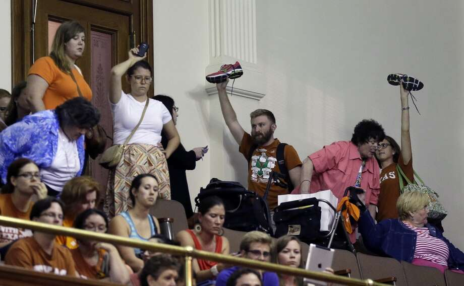 Spectators hold up their own shoes. Photo: Eric Gay, Associated Press