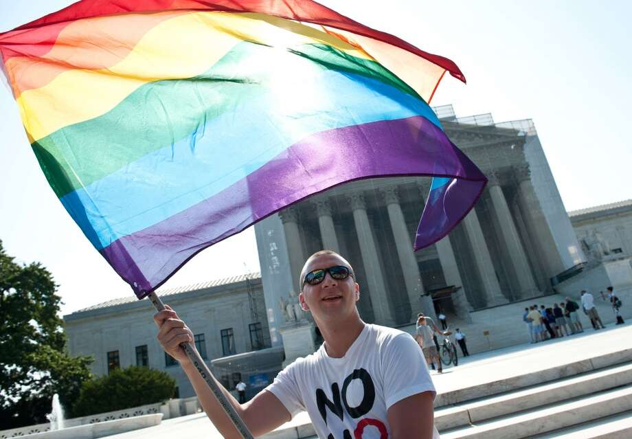 A gay rights activist waves a rainbow flag in front of the US Supreme Court in Washington,DC on June 25, 2013.   The high court convened again today to rule on some high profile decisions including including two on gay marriage and one on voting rights.  AFP PHOTO/Nicholas KAMMNICHOLAS KAMM/AFP/Getty Images