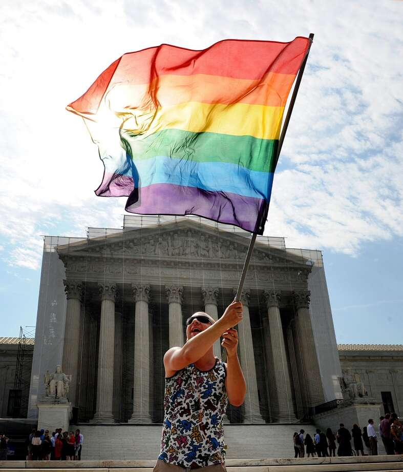 A demonstrator waves a flag in front of the U.S. Supreme Court on Monday, June 24, 2013, in Washington, DC. The court is expected to rule on a case on the Defense of Marriage Act and other gay rights issues this week. (Olivier Douliery/Abaca Press/MCT)