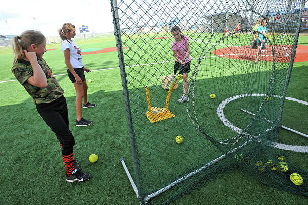 Lamar coach Megan Rowe, center, instructs Anna Kibodeaux, 10, on batting technique while Emma Humplik, 10, watches on during Lamar's softball camp on Tuesday. The cardinals will host another softball camp on July 16 and 17.  Photo taken Tuesday, June 25, 2013 Guiseppe Barranco/The Enterprise