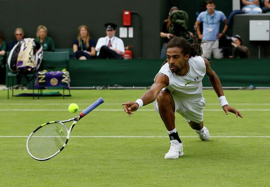 Dustin Brown of Germany tries to return the ball by throwing his racquet as he faces Lleyton Hewitt of Australia during their Men's second round singles match at the All England Lawn Tennis Championships in Wimbledon, London, Wednesday, June 26, 2013. Photo: Kirsty Wigglesworth