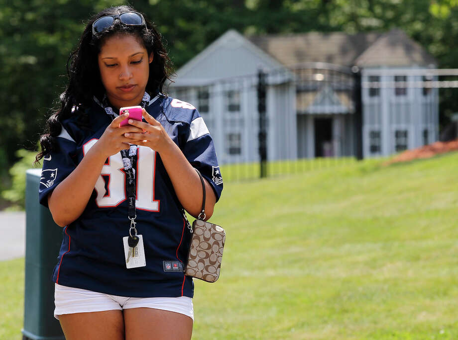 Maria Grullon, 19, of Worcester, drove to North Attleborough to see New England Patriots player Aaron Hernandez's home. She wears his jersey as she stands outside of his home in North Attleborough, Mass., June 23, 2013. Hernandez has been linked to the ongoing murder investigation of Odin Lloyd, 27, of Dorchester.  No charges have yet been filed against Hernandez. Photo: Boston Globe, Boston Globe Via Getty Images / 2013 - The Boston Globe