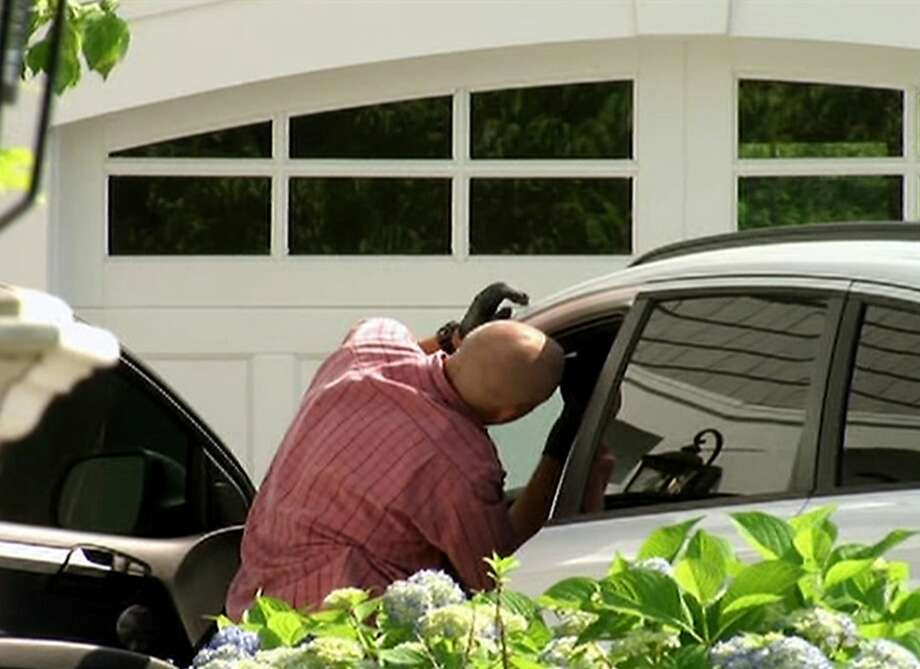 In this image taken from video, police search a car outside the home of New England Patriots football player Aaron Hernandez, Saturday, June 22, 2013, in North Attleboro, Mass. State police officers and dogs searched Hernandez's home as they investigate the killing of Odin Lloyd, a semi-pro football player whose body was found nearby. (AP Photo/ESPN)