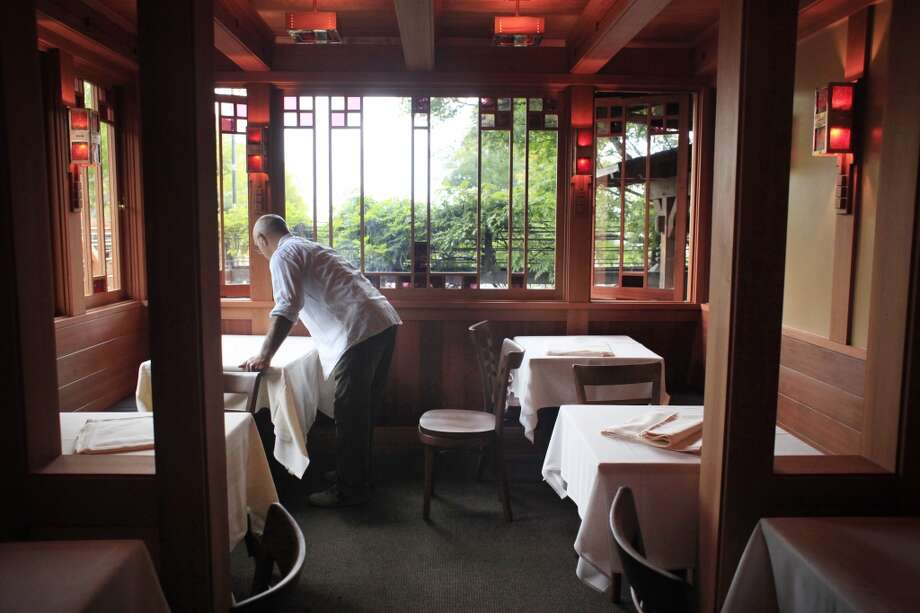 Chez Panisse waiter Gianni Benecchi sets the tables in the newly redone dinning room porch on the first night of business since March.