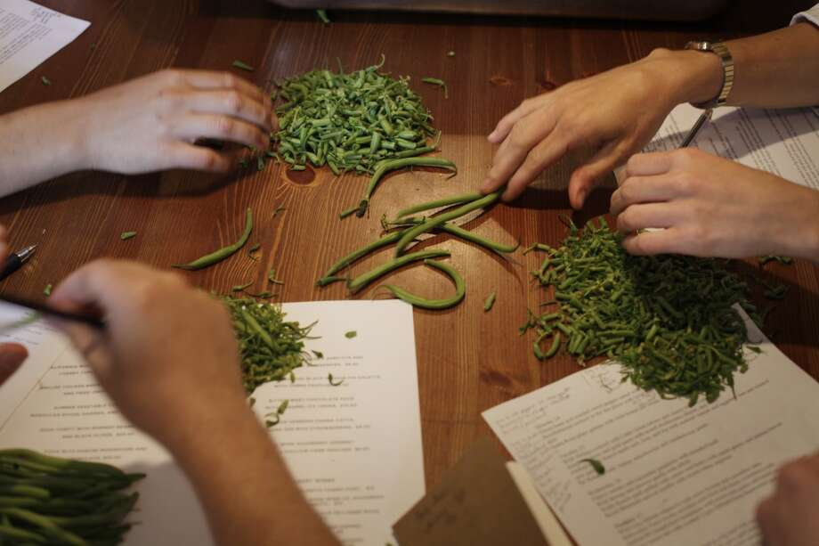Kitchen staff preps beans for the first meals to go out on Monday, opening night.