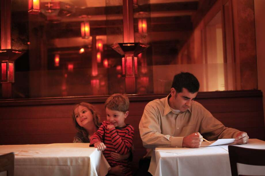 With his children, Claire, 7, and Matteo, 5, by his side, floor manager Noel Diaco goes over the evening's reservations.