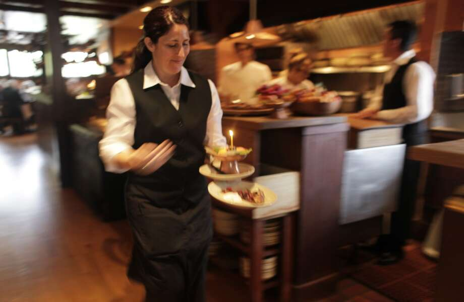 Server Amber Lawrence sends a birthday desert to the cafe floor on opening day.