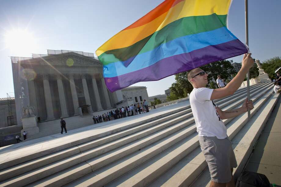Vin Testa of Washington waves a rainbow flag in support of gay rights outside the Supreme Court in Washington, Tuesday, June 25, 2013, as key decisions are expected to be announced. The Supreme Court resolved five cases, including affirmative action, on Monday. That leaves disputes about gay marriage and voting rights among the six remaining cases. The justices are meeting again Tuesday to issue some opinions and will convene at least one more time. Photo: J. Scott Applewhite