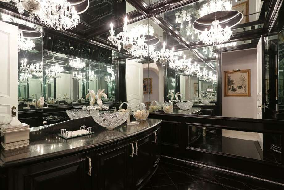 This formal Powder Room--one of five Powder Rooms in the home--sparkles with black lacquer and crystal. It will hearken you back to a powder room you visited in a luxurious Paris nightspot.