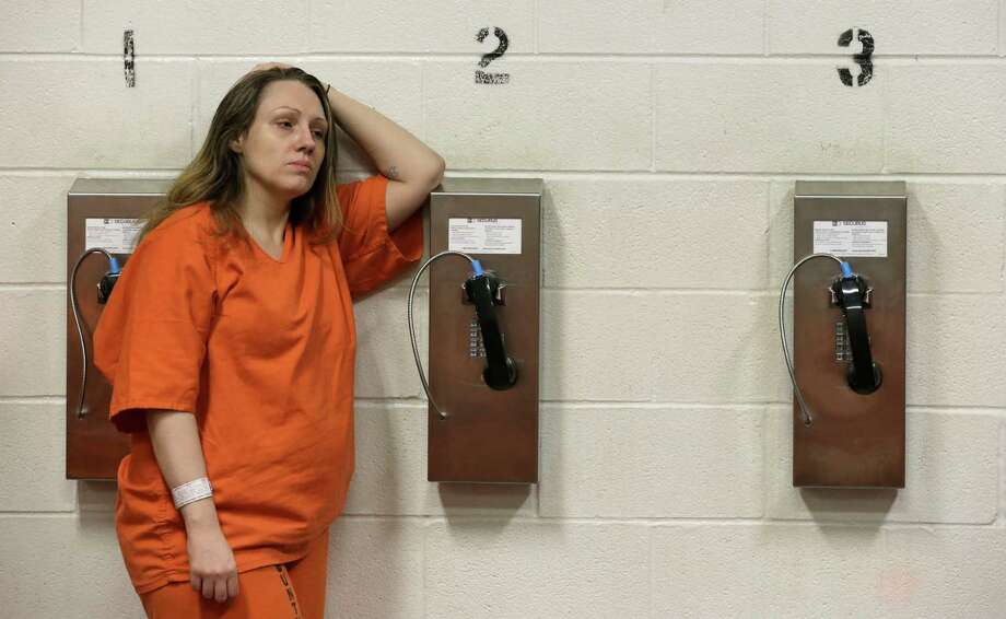 Harris County inmate Kristi Leonard leans against a telephone in her cell block Tuesday, June 4, 2013, in Houston. Arrested numerous times for prostitution, Leonard is part of a rehabilitation program called We've Been There Done That. (AP Photo/Pat Sullivan) Photo: Pat Sullivan, STF / AP