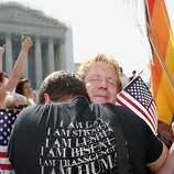 Michael Knaapen, left, and his husband John Becker, right, embrace outside the Supreme Court in Washington, Wednesday, June 26, 2013 after the court struck down a federal provision denying benefits to legally married gay couples.